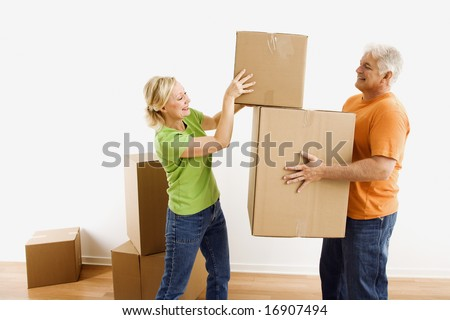 Middle-aged man holding cardboard moving boxes while woman places one on stack. - stock photo