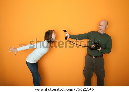 Middle-aged man holds telephone while woman screams at it - stock photo