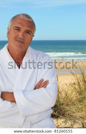 Middle aged man in a toweling robe by the sea
