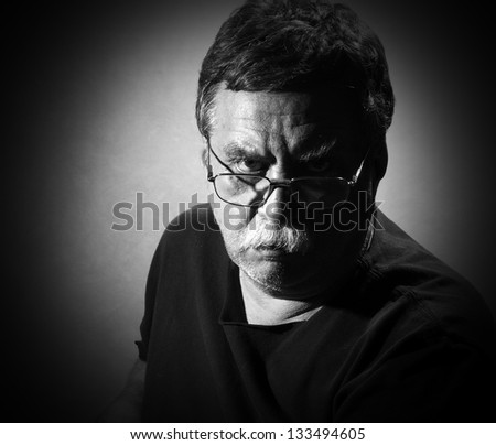 middle-aged man in eyeglasses looking to the camera - stock photo