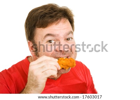 Middle aged man in football jersey enjoying a tasty fried buffalo wing.  Isolated on white.