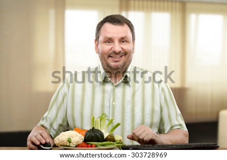 Middle-aged man is sitting at the table with fresh vegetables. He is on-line learner of nutritionist. The man is interesting to know what foods to eat in order to weight loss. - stock photo