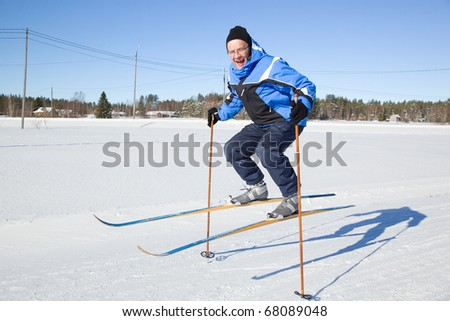 Middle-aged man jumping in the air with skis - stock photo