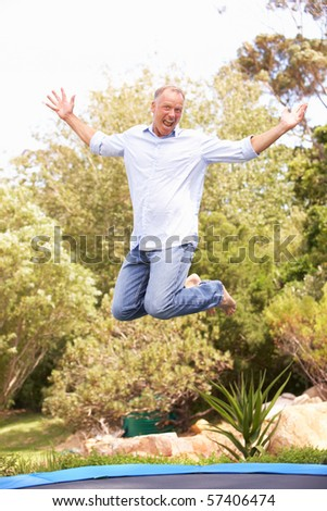 Middle Aged Man Jumping On Trampoline In Garden - stock photo