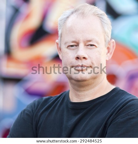Middle aged man leaning on a graffiti wall in the city - stock photo