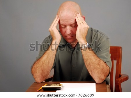 Middle Aged Man Looking Stressed Over Calculator - stock photo