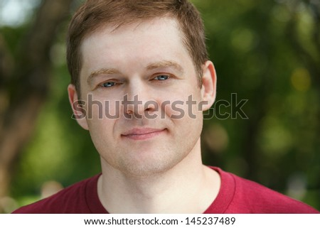 Middle-aged man looking to the camera in the park. Close up portrait. - stock photo