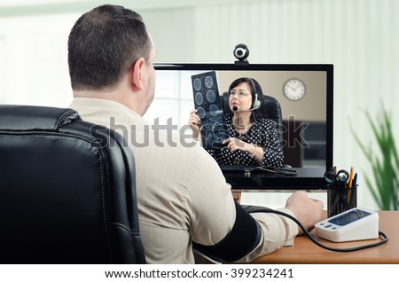 Middle-aged man measures his blood pressure in front of virtual doctor. In the meantime, telemedicine physician is carefully looking at his brain x ray picture in the monitor. Horizontal shot - stock photo