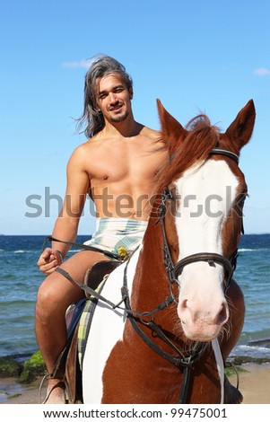 Middle-aged man on a horse on a summer day at the beach - stock photo