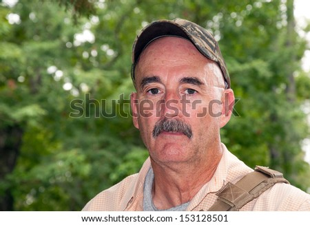 Middle aged man outdoors, hiking in woods in summer