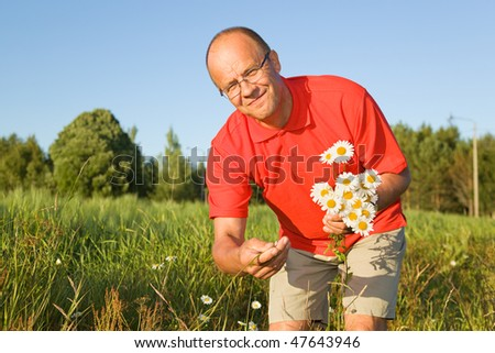 Middle-aged man picking up flowers - stock photo