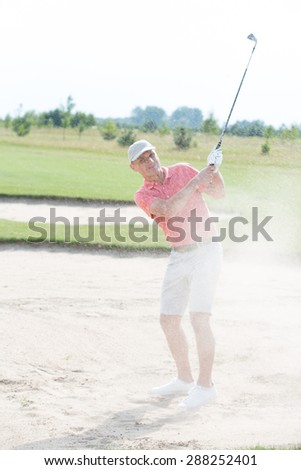 Middle-aged man playing at golf course - stock photo