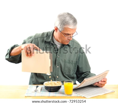 Middle aged man pouring cereal into his bowl while reading the morning newspaper. Square format isolated on white.
