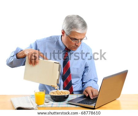 Middle aged man pouring his breakfast cereal into bowl. He is is busy working on his laptop computer and not paying attention to what he is doing. Horizontal format isolated over white.