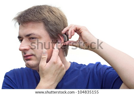 Middle-aged man putting on his hearing aid. Isolated on white - stock photo