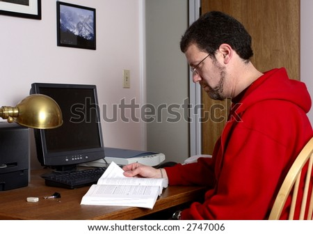 Middle-aged man reading a book in a home office.