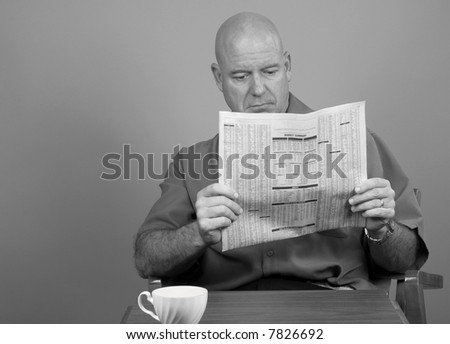 Middle Aged Man Reading Financial Section of Newspaper - stock photo