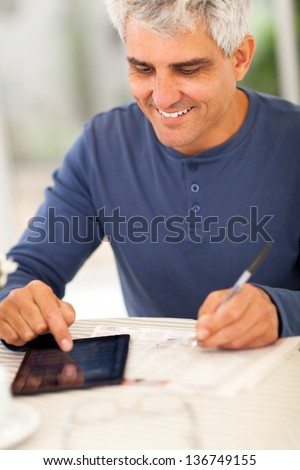 middle aged man reading newspaper and making notes on tablet computer - stock photo