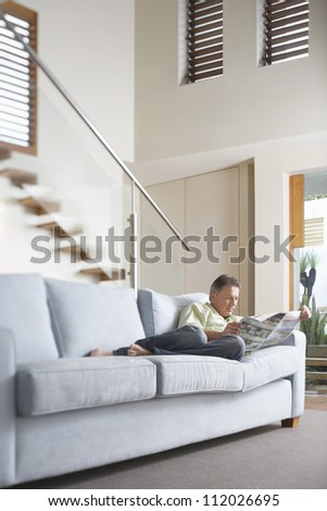 Middle aged man reading newspaper on sofa at home