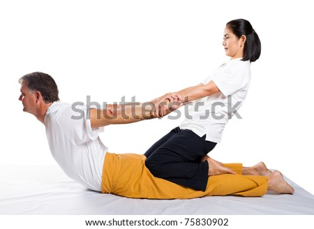 middle aged man receiving massage by therapist in traditional Thai position - stock photo