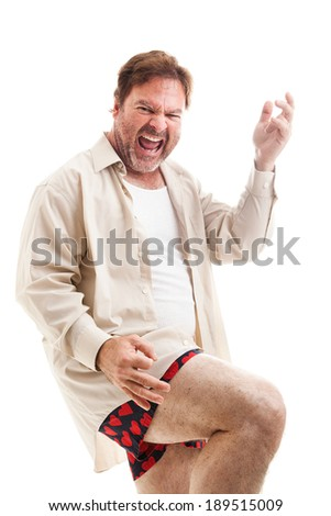 Middle-aged man rocks out playing air guitar in his underwear.  Isolated on white.