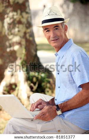 Middle-aged man sat in park with laptop - stock photo