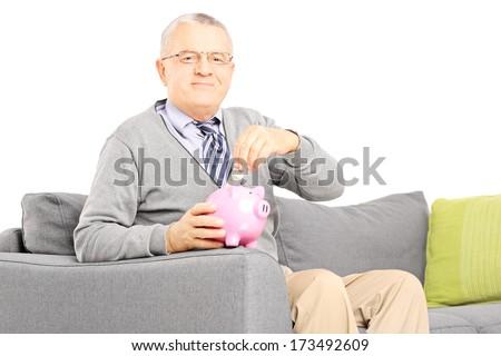 Middle aged man seated on sofa putting money into piggybank, isolated on white background - stock photo