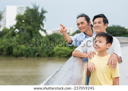 Middle-aged man showing something interesting to his father and son while standing on the bridge - stock photo