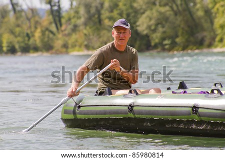 middle aged man sits in rubber dinghy paddle in hand on a river in pretty natural summer settings
