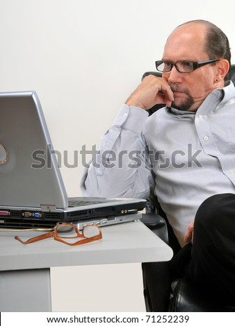 Middle aged man sitting at his desk looking at his computer in an office setting. He is concentrating on what he sees on his laptop. - stock photo