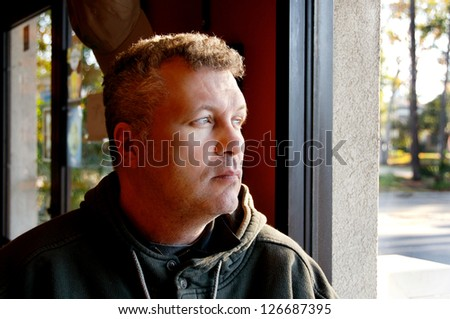 Middle aged man sitting by a window in a restaurant. - stock photo