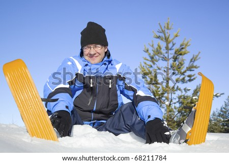 Middle-aged man sitting in snow - stock photo