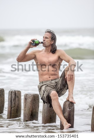 Middle-aged man sitting near the sea and drinking alcohol - stock photo