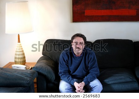 Middle aged man sitting on a couch alone by a telephone.