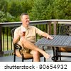 Middle aged man sitting on cast aluminium garden table on deck and drinking a glass of beer in back yard - stock photo