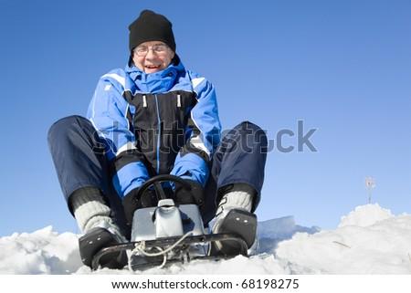 Middle-aged man sledding - stock photo