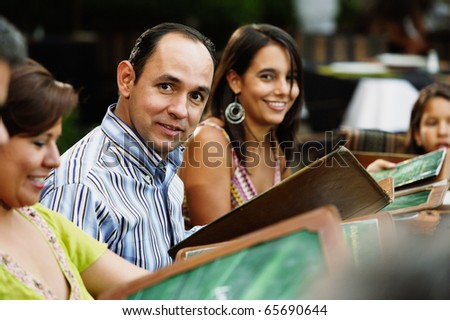 Middle-aged man smiling for the camera at a restaurant - stock photo