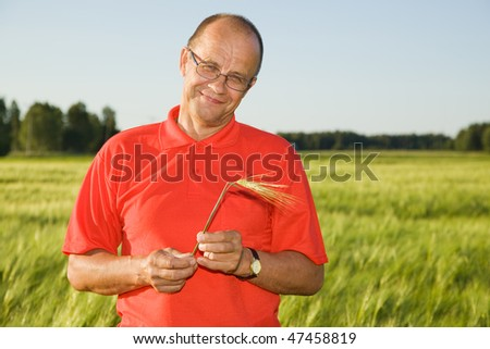 Middle-aged man smiling on a field - stock photo