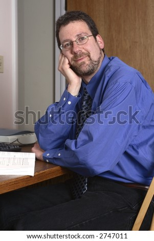 Middle-aged man smiling, with his head in his hand. - stock photo