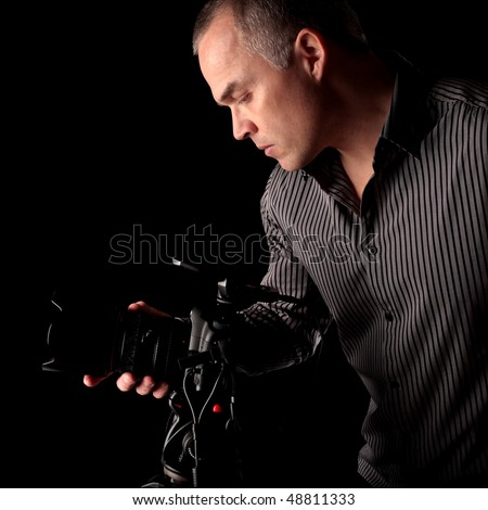 Middle aged man taking a photograph with a digital SLR camera in the dark with black background - stock photo