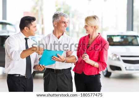middle aged man talking to wife before buying a new car at dealership - stock photo