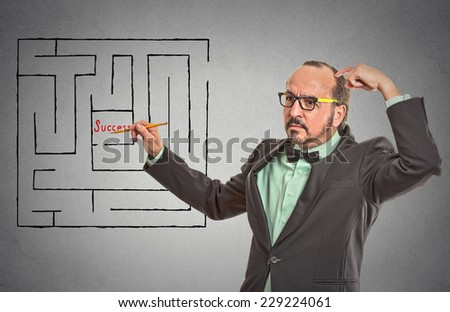 Middle aged man thinking looking for path through labyrinth to reach success isolated grey wall office background. leadership guidance idea skills concept. Guy scratching head pensive solving problem  - stock photo