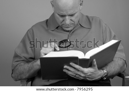Middle Aged man using magnifier to read book - stock photo