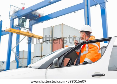 Middle-aged man using walkie-talkie while standing at car door in shipping yard