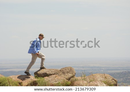 Middle aged man walking on top of a mountain - stock photo