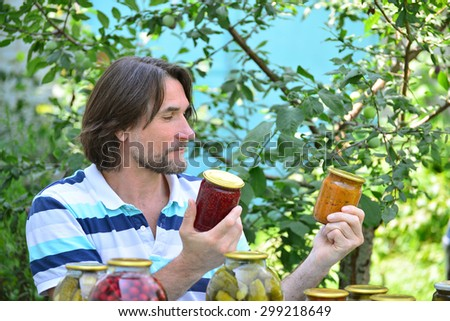 Middle-aged man with canned vegetables, the prepared for winter - stock photo