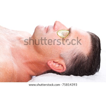 middle aged man with cucumber facial mask in spa