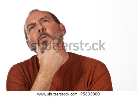 middle aged man with hand on beard looking up thinking - stock photo
