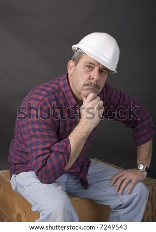 Middle-aged man  with hardhat on sitting on a wooden crate in thought. - stock photo