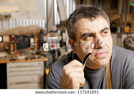 Middle-aged man with smoking pipe sitting in his workshop and looking sideways - stock photo